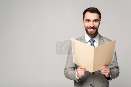 Photo for Positive businessman smiling at camera while holding paper folder isolated on grey - Royalty Free Image