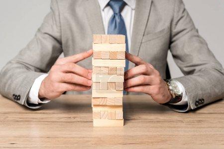 Photo pour Vue recadrée de l'homme d'affaires jouant blocs tour de bois jeu isolé sur gris - image libre de droit