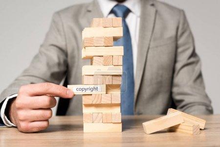 Photo pour Vue recadrée de l'homme d'affaires jouant blocs tour en bois jeu avec inscription de copyright isolé sur gris - image libre de droit