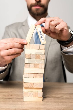 Photo for Partial view of businessman playing blocks wood tower game with copyright inscription isolated on grey - Royalty Free Image