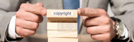 Photo pour Vue recadrée d'un homme d'affaires tenant un bloc de bois avec inscription de copyright isolé sur gris - image libre de droit