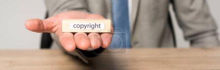 Photo pour Vue recadrée d'un homme d'affaires tenant un bloc de bois avec inscription de copyright isolé sur une photo panoramique grise - image libre de droit