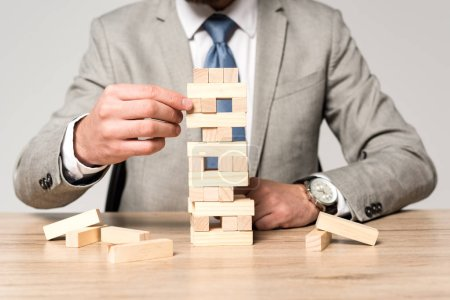 Photo for Cropped view of businessman playing blocks wood tower game isolated on grey - Royalty Free Image