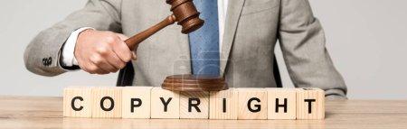 Photo pour Crochet vue du juge tenant le marteau près de cubes en bois avec inscription du droit d'auteur isolé sur fond gris, photo panoramique - image libre de droit