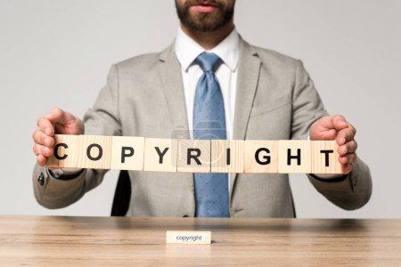 abgeschnittene Ansicht eines Geschäftsmannes mit Holzwürfeln und Worturheberrecht isoliert auf grau