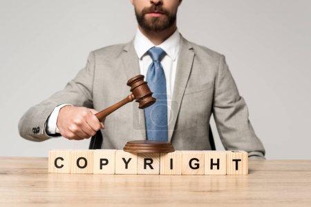 Photo pour Crochet vue du juge tenant le marteau près de cubes de bois avec inscription de droit d'auteur isolée sur gris - image libre de droit