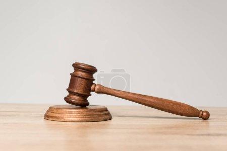 Photo pour Marteau sur un bureau en bois isolé sur gris avec espace de copie - image libre de droit