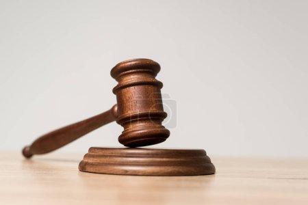Photo pour Foyer sélectif du marteau sur un bureau en bois isolé sur gris - image libre de droit