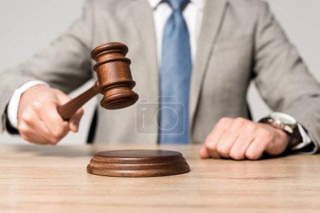 Photo pour Crochet vue du juge tenant son marteau alors qu'il est assis à un bureau isolé sur gris - image libre de droit