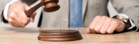 Photo pour Vue recadrée du juge tenant un marteau alors qu'il était assis au bureau isolé sur une photo panoramique grise - image libre de droit