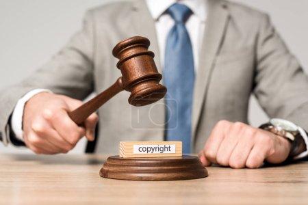 Photo pour Vue recadrée du juge tenant un marteau près d'un bloc de bois avec inscription de copyright isolée sur gris - image libre de droit