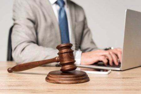 Photo pour Foyer sélectif de marteau près avocat travaillant à l'ordinateur portable isolé sur gris - image libre de droit