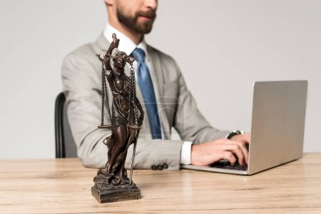 Photo pour Vue partielle d'un avocat utilisant un ordinateur portatif près de lui statue isolée sur gris - image libre de droit