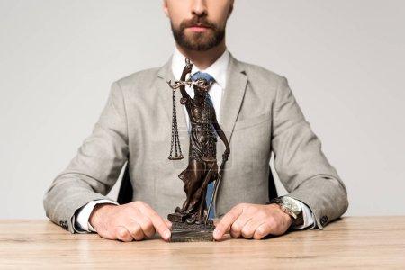 Photo pour Vue partielle d'un avocat montrant une statue alors qu'il était assis à un bureau isolé sur un fond gris - image libre de droit