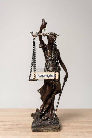 Photo pour Statue themis et bloc de bois avec copyright mot sur écailles sur bureau en bois isolé sur gris - image libre de droit