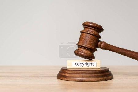 Photo pour Marteau et bloc de bois avec inscription de copyright sur bureau en bois isolé sur gris - image libre de droit