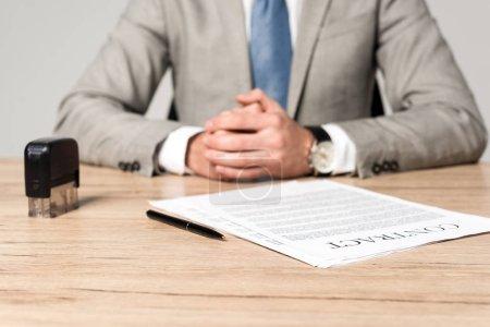 Photo pour Vue recadrée de l'homme d'affaires assis au bureau près du contrat, timbre et stylo isolés sur gris - image libre de droit