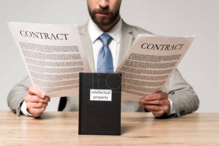 Photo pour Vue recadrée des contrats de lecture d'homme d'affaires près du livre avec titre de propriété intellectuelle isolé sur gris - image libre de droit