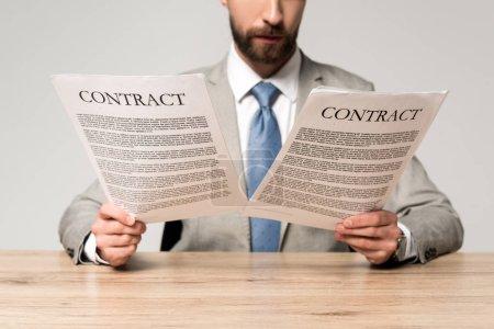 Photo pour Crochet vue d'un homme d'affaires lisant des contrats assis à son bureau isolé sur fond gris - image libre de droit