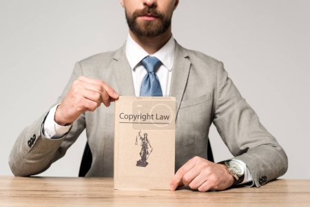 Photo pour Vue partielle d'un avocat montrant un livre portant un titre de droit d'auteur isolé sur gris - image libre de droit