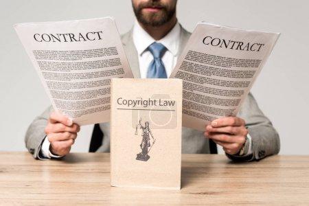 Photo pour Vue partielle d'un avocat regardant des contrats près du livre avec un titre de droit d'auteur isolé sur gris - image libre de droit