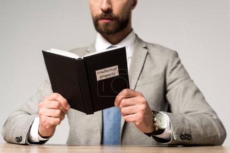 Photo pour Crochet vue d'un homme d'affaires lisant un livre juridique dont le titre de propriété intellectuelle est isolé sur fond gris - image libre de droit