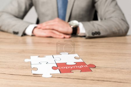 cropped view of businessman sitting at desk near jigsaw puzzle with word copyright isolated on grey