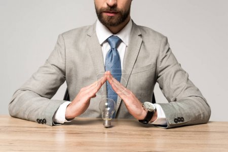 Foto de Vista parcial de los hombres de negocios que muestran un gesto de protección sobre las bombillas aisladas en gris - Imagen libre de derechos