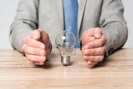 Photo pour Vue partielle d'un homme d'affaires montrant un geste de protection près d'une ampoule isolée sur gris - image libre de droit