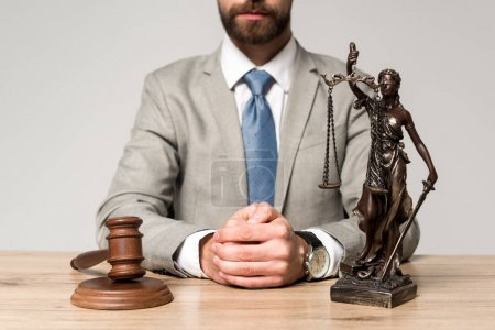Photo pour Vue partielle du juge assis au bureau près du marteau et statue de themis isolé sur gris - image libre de droit