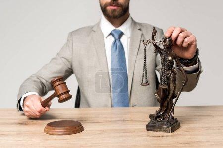 Photo pour Vue partielle du juge tenant le marteau et sa statue isolée sur gris - image libre de droit