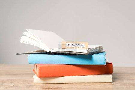 Photo pour Empilage de livres, cahier ouvert et bloc de bois avec droit d'auteur sur un bureau en bois isolé sur gris - image libre de droit