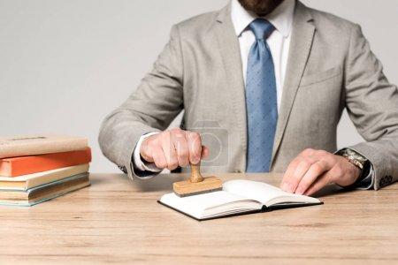 Photo pour Vue partielle de l'avocat apposant son timbre dans un carnet isolé sur gris - image libre de droit