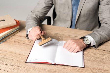 Photo pour Crochet vue d'un avocat apposant le timbre dans un cahier isolé sur gris - image libre de droit