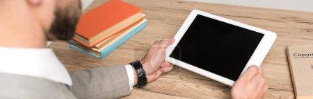 Photo pour Vue partielle d'un homme d'affaires tenant une tablette numérique avec écran vierge isolé en gris, prise de vue panoramique - image libre de droit