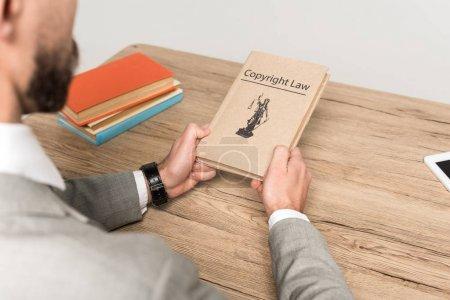 Photo pour Vue recadrée de l'avocat détenant un livre juridique avec titre de la loi sur le droit d'auteur isolé sur gris - image libre de droit