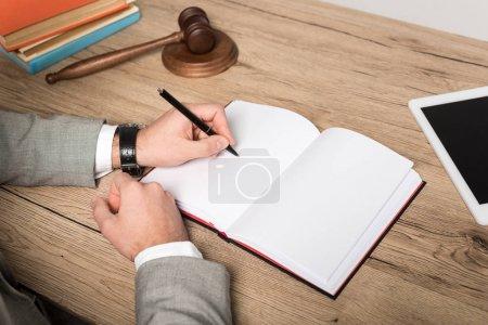 Photo pour Crochet vue d'un avocat écrivant dans un cahier sur un bureau en bois - image libre de droit