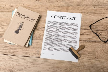 Photo pour Top view of contract, stamp, legal books and glasses on wooden desk - image libre de droit
