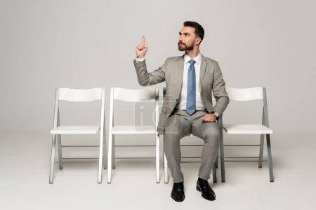 Foto de Un hombre de negocios confiado que ocupa la presidencia y muestra un gesto de idea sobre fondo gris - Imagen libre de derechos