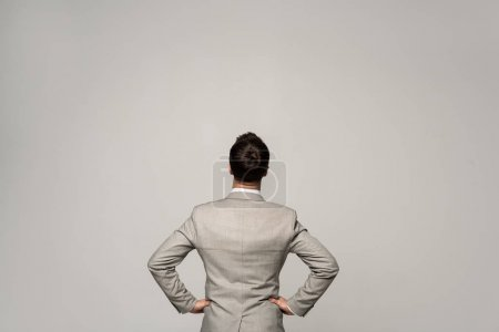 Photo for Back view of businessman standing with hands on hips isolated on grey - Royalty Free Image