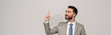 Photo for Panoramic shot of smiling businessman showing idea gesture isolated on grey - Royalty Free Image