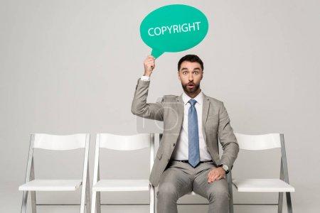 Photo pour Surpris homme d'affaires tenant la bulle de la pensée avec le mot copyright assis sur une chaise sur fond gris - image libre de droit