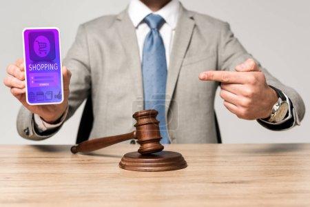 Photo pour Crochet vue d'un avocat pointant du doigt vers un smartphone avec une application de magasinage, et marteau sur le bureau - image libre de droit