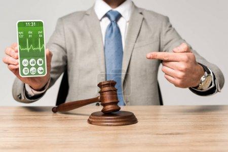 Photo pour Croustillant vue d'un avocat pointant du doigt vers un smartphone avec une application rythmique, et marteau sur le bureau - image libre de droit