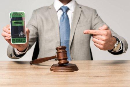 Photo pour A vu un avocat pointer du doigt sur un smartphone avec une application de réservation, et le marteau du juge sur le bureau - image libre de droit