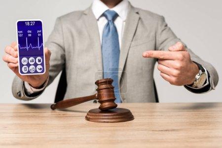 Photo pour Crochet vue d'un avocat pointant du doigt vers un smartphone avec un rythme cardiaque app et juge marteau sur le bureau - image libre de droit