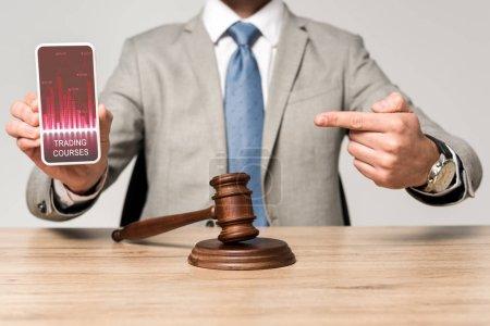 Photo pour Crochet vue d'un avocat pointant du doigt vers un smartphone avec application de cours de trading et marteau du juge sur le bureau - image libre de droit