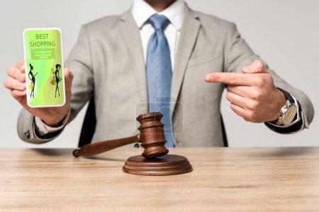 Photo pour Crochet vue d'un avocat pointant du doigt vers un smartphone avec la meilleure application de magasinage, et le marteau du juge sur le bureau - image libre de droit