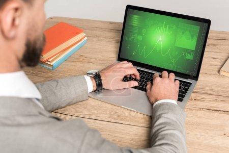 Photo pour Vue partielle d'un homme d'affaires utilisant un ordinateur portatif avec de l'information de marketing à l'écran isolée sur gris - image libre de droit