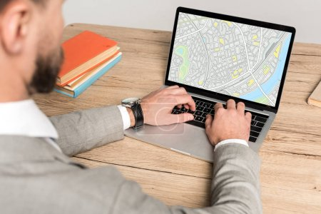 vista recortada del hombre de negocios utilizando el ordenador portátil con mapa en la pantalla aislada en gris